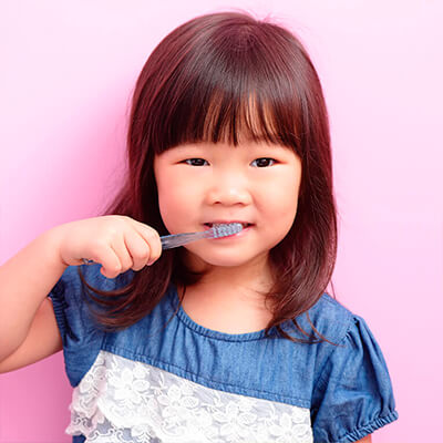 A toddler brushes her teeth