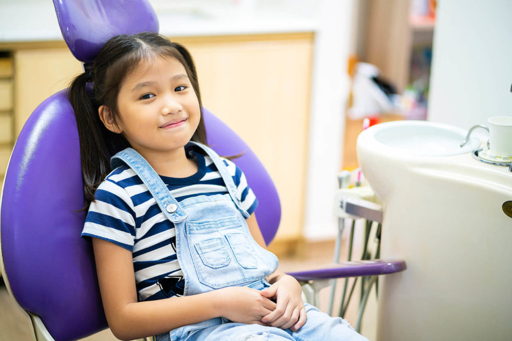 A young dental patient sits in an exam chair waiting for her checkup